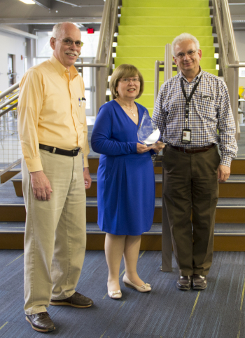 MCC President Susan Huard holds the trophy, which the Center for Digital Education presented to (left) George Waggoner, MCC Computer Science faculty and former director of IT and (right) Peter LaMonica, chair of MCC Computer Science department and cybersecurity instructor.