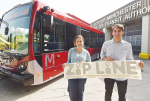 Manchester Community College students Emily Rentz, from Milford, who created the new Manchester Transit Authority bus logo and colors poses with Thomas Campbell, from Pembroke, who designed and created the Zip Line logo idea by a new bus during the rebranding unveiling for the Manchester Transit Authority in Manchester on Friday.