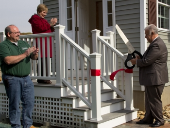 Manchester Mayor Ted Gatsas cuts the ribbon on the new home built on Straw Road by students of Manchester Community College.