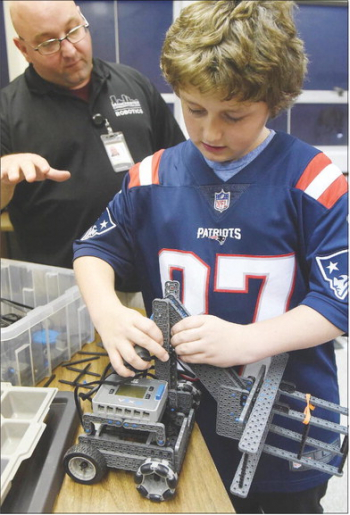Mannix Muir, a seventh-grader, is helped with his VEX IQ robot by Dan Larochelle, from Manchester Community College, at St. Joseph Regional High School in Manchester on Wednesday.