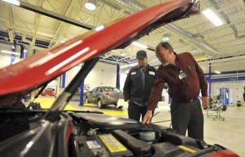 Professor Peter Ashworth, right, and alumnus Greg Landry examine a 2002 Lexus SC 430 during the opening of the first phase of the automotive technology training center at Manchester Community College.